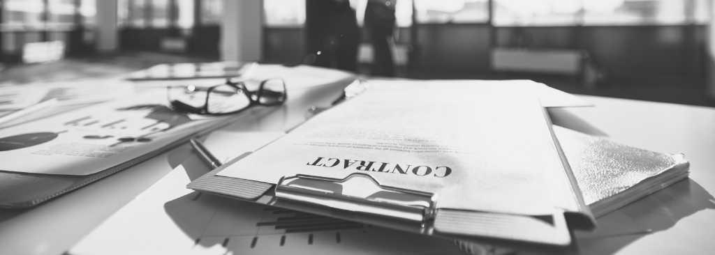 Un'immagine in bianco e nero, in primo piano una scrivania ricolma di documenti, occhiali da vista, e nello sfondo sfocato si intravede una vetrata con delle persone che stanno parlando tra loro. Nel taglio centrale dell'immagine, messo a fuoco, la presenza di una cartella con la scritta contract.